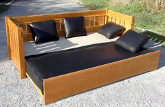 Shown open with top cushion lowered to become a bed.