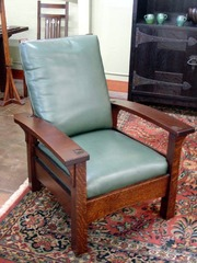 Additional view of same form in a lighter stain with green leather upholstery.