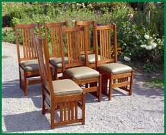 Set of six dining chairs in a light stain color, upholstered in a light green leather.