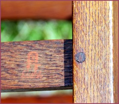 Red decal signature and pinned mortise & tenon joint at rear of chair.