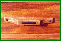 Close-up drawer pull with ebony detail.