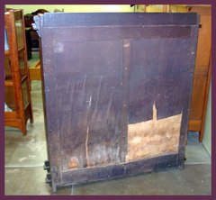 View of back, showing the paper label in the upper left hand corner and the moisture damage affecting only the floating panel of the frame and panel back. No damage to the panel's frame or the frame or feet of the bookcase.