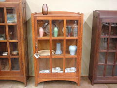 Shown between a Gustav Stickley arched china cabinet to the left and an early mitered-mullion bookcase to the right.