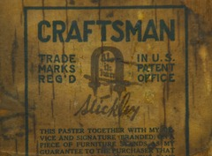Close up Gustav Stickley signature paper label and guarantee on back of cabinet.