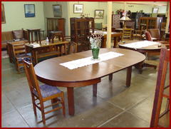 "Partial view of the ""Craftsman Antique"" side of the shop, table shown with all four leaves installed."