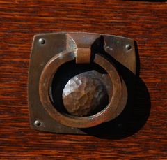 Detail early style hand hammered drawer pull.