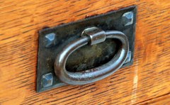 Detail Gustav Stickley early hand hammered oval iron pull with pyramidal screws circa 1904 to 1906.