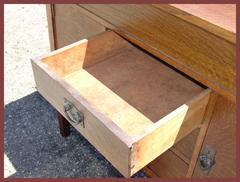 "The upper middle drawer open showing the original ""ooze leather"" covering the interior."