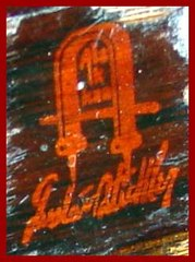 "Close-up of the Gustav Stickley red decal signature on the back of the rear stretcher. ""Gustav Stickley"" in script below the craftsman joiners mark surrounding the words: ""Als Ik Kan"", translated: .....""as I can"" or ""to the best of my ability"""