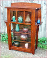 Replica Limbert china cabinet with elongated corbles supporting exterior shelves.